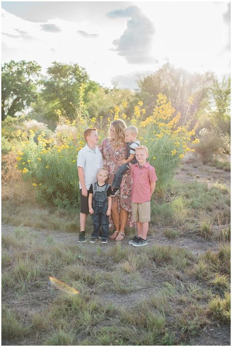 Mom with her four boys in the glow of sunset for family pictures.